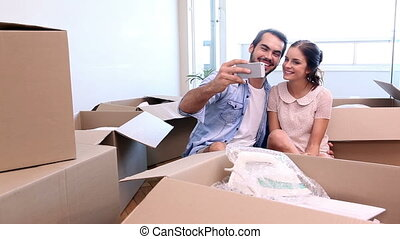 Attractive couple taking a selfie together in their new home