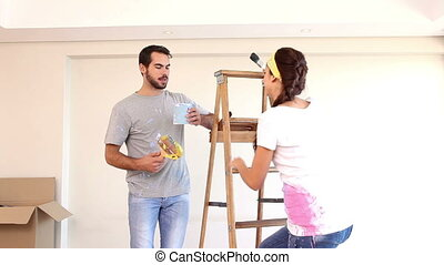 Attractive couple painting their living room in their new...