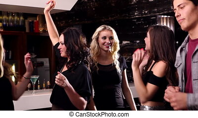 Attractive friends dancing together on the dance floor at...