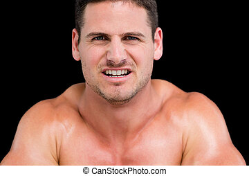 Close up portrait of a young muscular man over black...