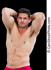 Portrait of a shirtless muscular man posing over black...
