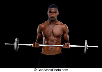Portrait of a serious fit young man lifting barbell over...