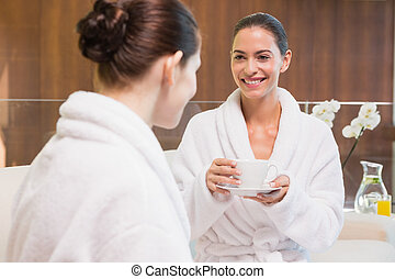 Smiling women in bathrobes having tea - Two smiling young...