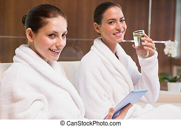 Women in bathrobes drinking water and text messaging - Young...