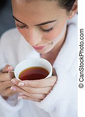 Beautiful woman in bathrobe having tea - Close up of a...