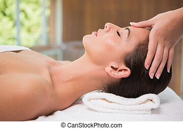 Attractive woman receiving head massage at spa center - Side...