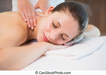 Attractive woman receiving back massage at spa center - Side...