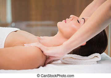 Attractive woman receiving shoulder massage at spa center -...