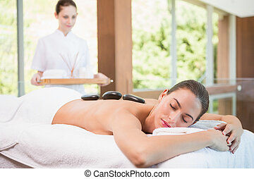 Beautiful woman receiving stone massage at health farm -...