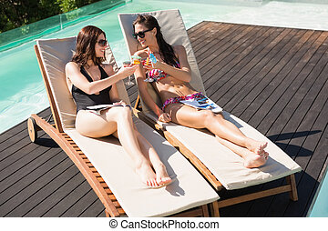 Women toasting drinks by swimming pool - Two beautiful young...