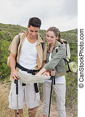 Couple looking at map on mountain terrain