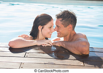 Couple in swimming pool on a sunny day - Smiling romantic...