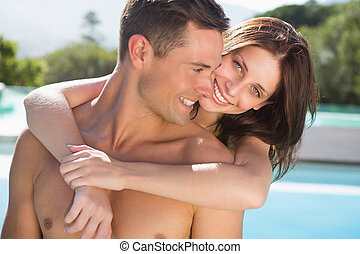 Romantic woman embracing man by swimming pool - Portrait of...