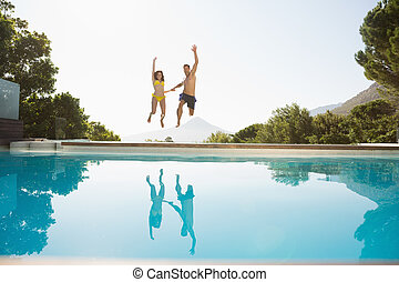 Cheerful couple jumping into swimming pool - Full length of...
