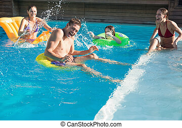 People playing in the swimming pool - Cheerful young people...