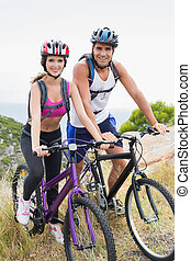 Athletic couple mountain biking - Portrait of an athletic...