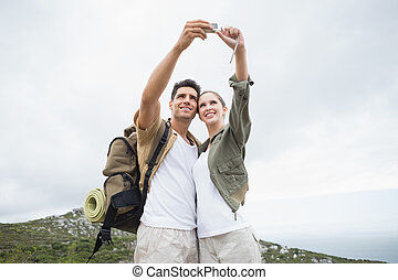 Hiking couple taking picture of themselves on mountain...