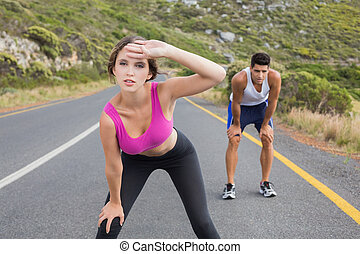 Fit young couple running on road - Fit young couple running...