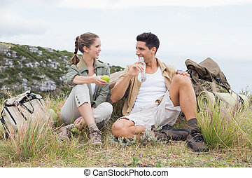 Couple taking break after hiking uphill - Young couple...