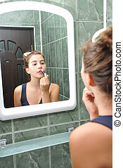 Girl in bathroom mirror - A beautiful teen girl putting...