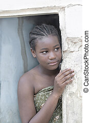 Young Afro beauty at the door of her house