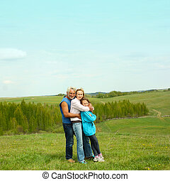 portrait of a grandfather, daughter and granddaughter on the background  attractive landscape. Family of three generations.