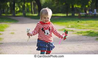 little girl runing with blowballs and toy