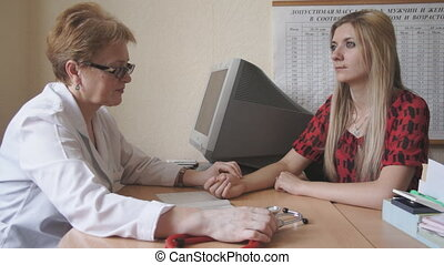 doctor measures the pulse of women - Doctors office inspects...