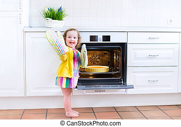 Toddler girl with an apple pie in the oven - Adorable...