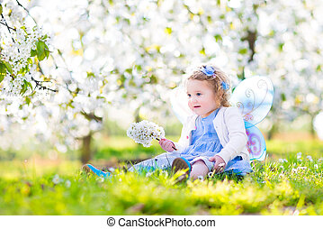 Curly toddler girl in fairy costume playing in fruit garden...