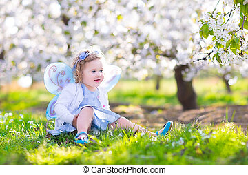 Happy toddler girl in fairy costume in spring apple garden -...