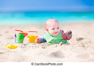 Funny baby playing on the beach - Adorable happy laughing...