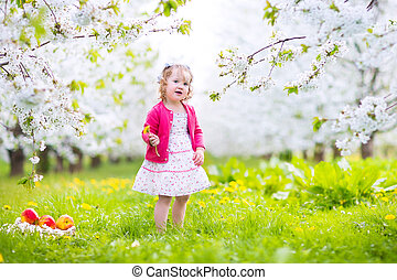 Cute toddler girl eating apple in a blooming garden -...