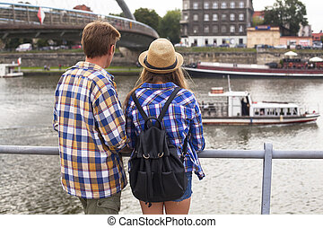 Young couple on a journey to Europe, standing on the bank of...
