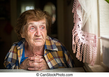 Old woman sitting at a table in his house, with a worried...