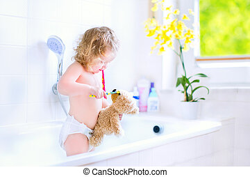 Baby girl brushing teeth playing with a teddy bear - Happy...