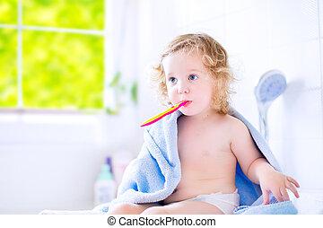 Toddler girl brushing teeth - Funny toddler girl with curly...