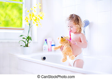 Cute toddler girl brushing teeth with a toy - Happy funny...