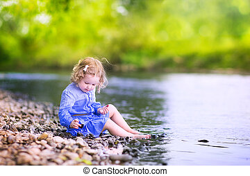 Little girl playing at river shore - Adorable curly toddler...