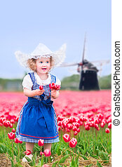 Girl in national costume in tulips - Adorable curly toddler...