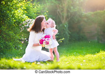 Happy mother and her daughter in the garden - Beautiful...