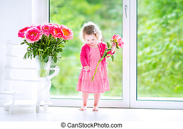 Toddler girl playing with peony flowers - Cute happy toddler...
