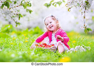 Toddler girl eating strawberry in blooming garden - Adorable...