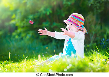 Toddler girl playing with butterfly - Happy laughing little...