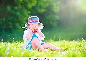 Toddler girl eating an aple in the garden - Happy beautiful...