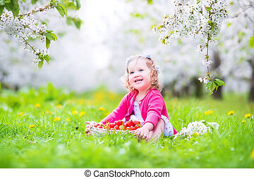 Toddler girl eating strawberry in blooming garden - Cute...