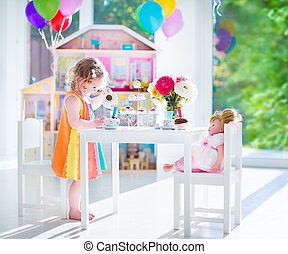 Toddler girl playing tea party with a doll - Adorable...