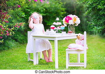 Toddler girl playing tea party with a doll - Adorable funny...