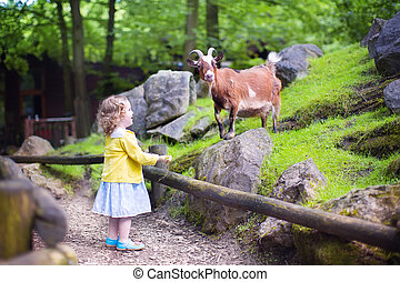 Little girl feeding a goat - Cute little toddler girl with...