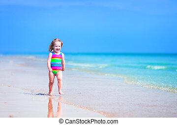 Little girl running on a beach - Happy laughing little girl...